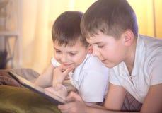 Två ungar som använder minnestavlaPC i sovrum Arkivfoton