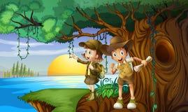 Två ungar som campar vid floden Royaltyfria Bilder