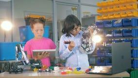 Två ungar som fixar en robot i ett laboratorium Innovativt begrepp för teknisk utbildning stock video
