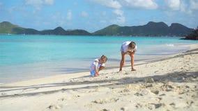 Två ungar som gör sandslotten och spelar på den tropiska stranden arkivfilmer
