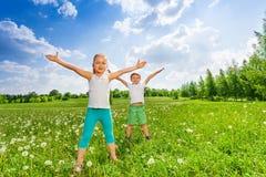 Två ungar som gör utomhus- gymnastik på gräset royaltyfria foton
