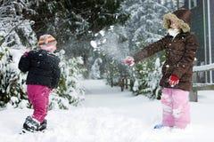 Två ungar som har ett kasta snöbollslagsmål fotografering för bildbyråer