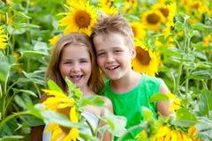 Två ungar som har gyckel bland solrosen royaltyfria bilder