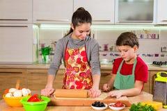 Två ungar som knådar degen som gör pizza Arkivbild