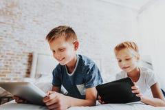 Två ungar som lägger i säng med digitala minnestavlor arkivfoton
