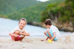 Två ungar som leker på stranden royaltyfri bild