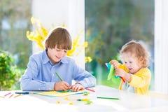 Två ungar som målar och klipper färgrika pappers- fjärilar royaltyfri foto