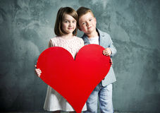 Två ungar som rymmer en jätte- hjärta Arkivbild