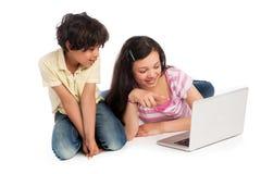 Två ungar som ser en bärbar datordator arkivbilder