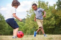 Två ungar som spelar fotboll royaltyfri fotografi