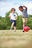 Två ungar som spelar fotboll Fotografering för Bildbyråer