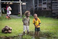 Två ungar som spelar i en pöl Arkivfoton