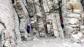 Två ungar som spelar i en Rocky Crag royaltyfri bild
