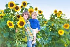 Två ungar som spelar i ett solrosfält på solig dag Royaltyfri Foto