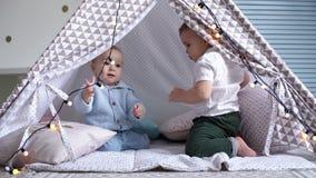 Två ungar som spelar med en girland i ett barns tält Man kryper i väg från andra lager videofilmer