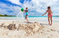 Två ungar som spelar med sand Arkivbild