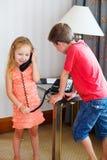 Två ungar som talar på, ringer Arkivbilder