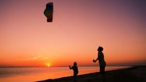 Två ungar som tillsammans lanserar regnbågedraken på solnedgången lager videofilmer