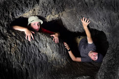 Två ungar som undersöker grottan royaltyfria foton