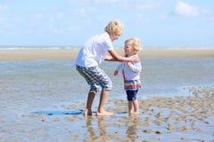 Två ungar, syskongrupp som spelar på stranden Royaltyfria Foton