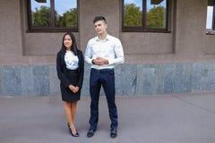 Två ungdomar, internationella studenter, meddelar, löser pro- Fotografering för Bildbyråer