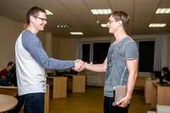 Två ungdomardiskuterar ett projekt i kontoret Skaka händer med de efter diskussionen och det vänliga leendet arkivbilder