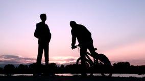 Två ungdomarskakar händer med de och säger farväl Sidor för en tonåring på en cykel och en annan grabb på två arkivfilmer