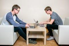 Två ungdomarsom arbetar på bärbara datorer i kontoret och att skriva ett program som korrigerar texten royaltyfri fotografi