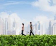 Två ungdomarsom bär arbeta i trädgården utrustning som går över ett grönt fält med växter, cityscape i bakgrunden royaltyfri bild