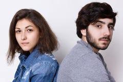 Två ungdomarsom tillbaka sitter för att dra tillbaka att se direkt in i kamera Ett ungt par: brunettflicka i jeankläder och stilf Royaltyfri Fotografi