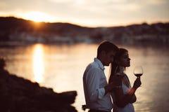 Två ungdomarsom tycker om ett exponeringsglas av rött vin i solnedgången på sjösidan Rött vin för od för sunt exponeringsglas som Arkivfoto