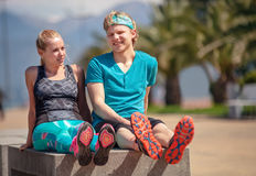 Två ungdomarvilar tillsammans på bänken, når de har joggat Arkivfoton