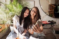 Två ungdomliga le härliga slanka flickor med långt mörkt hår, bärande tillfällig kläder, sitter bredvid de och tar a royaltyfri fotografi