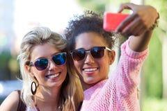 Två universitetflickastudenter som tar en selfie i gatan Royaltyfria Bilder