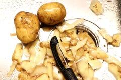 Två unpeeled potatislögner i en våt diskho bredvid potatishudar och en svart potatisskalare royaltyfria foton