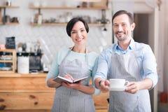 Två uppassare i förkläden som står i kafé Arkivfoto