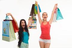 Två upphetsade flickor med shoppingpåsar royaltyfria bilder