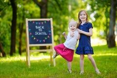 Två upphetsade lilla systrar vid en svart tavla Fotografering för Bildbyråer