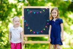 Två upphetsade lilla systrar vid en svart tavla Royaltyfria Foton