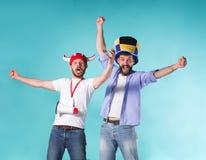 Två upphetsade manliga vänner firar hållande ögonen på sportar royaltyfria bilder