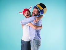 Två upphetsade manliga vänner firar hållande ögonen på sportar Arkivfoton