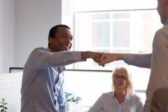 Två upphetsade olika manliga arbetare ger nävebulan för att fira teamwork royaltyfri fotografi
