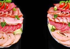 Två uppläggningsfat av skivad skinka, salami och kurerat kött på svart backgr Arkivfoto