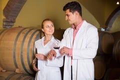 Två uppmärksamma vinhusarbetare som kontrollerar kvalitet av produkten arkivfoton