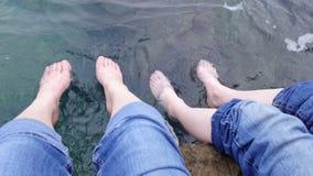 Två uppsättningar av fot som paddlar i havet, Kroatien arkivbilder