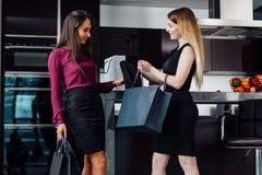 Två ursnygga kvinnor, når att ha shoppat hemma En flicka som visar hennes köp till en kvinnlig vän som hemma står royaltyfria foton