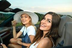 Två ursnygga modeller som poserar i cabriolet och att se camer och att le royaltyfri fotografi