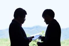 Två utövande affärsmän som diskuterar över ett projekt på en compute royaltyfri fotografi