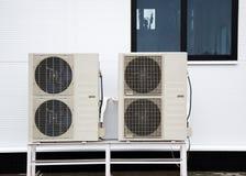 Två utomhus- enheter av luftkonditioneringsapparater som framme står på jordningen av fasaden av den moderna byggnaden Arkivfoto