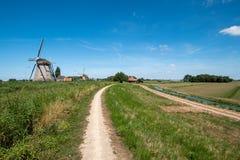 Två väderkvarnar på en fördämning längs polder nära Maasland, Nethen royaltyfri fotografi